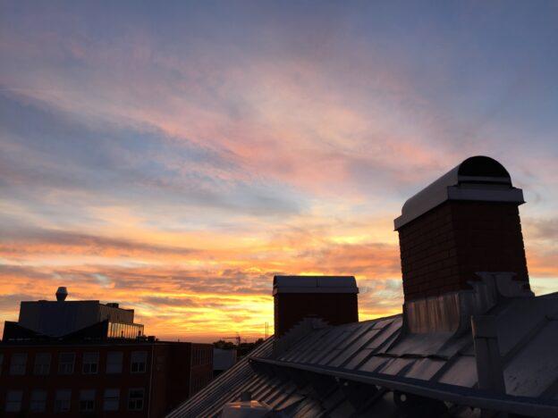 Solen går ner över Tolvmannahusets skorstenar.